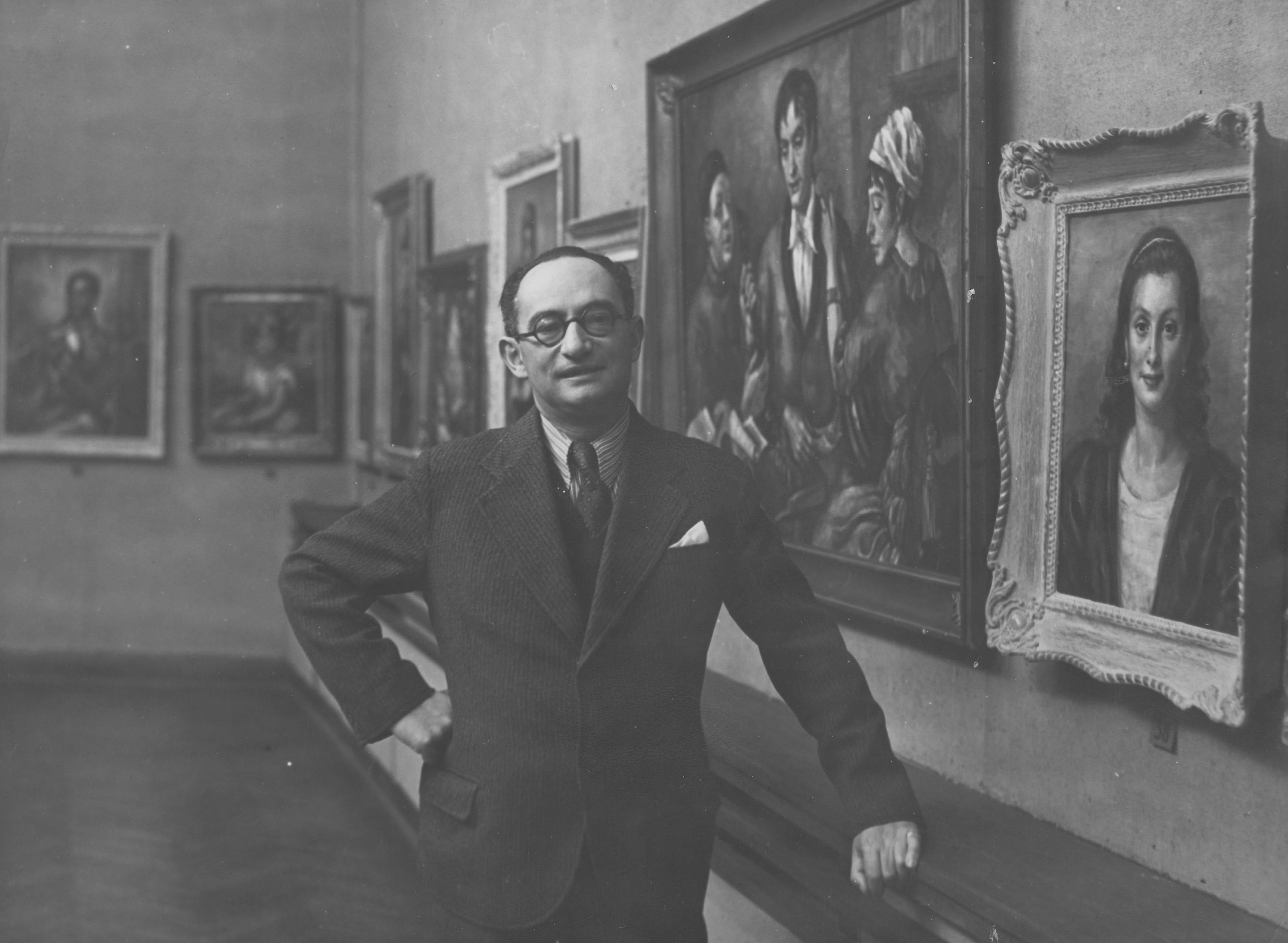 Roman Kramsztyk na tle wystawy swoich prac w Instytucie Propagandy Sztuki w Warszawie w 1932 roku, źródło: Narodowe Archiwum Cyfrowe