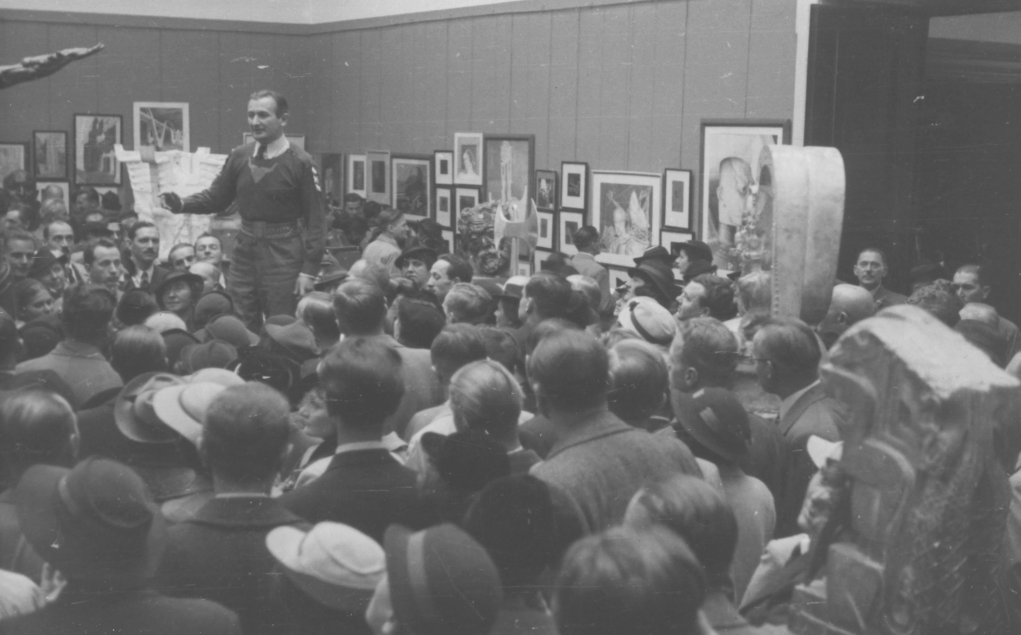 Stanisław Szukalski przemawia na wystawie w krakowskim TPSP, 1936 rok, źródło: nac.gov.pl