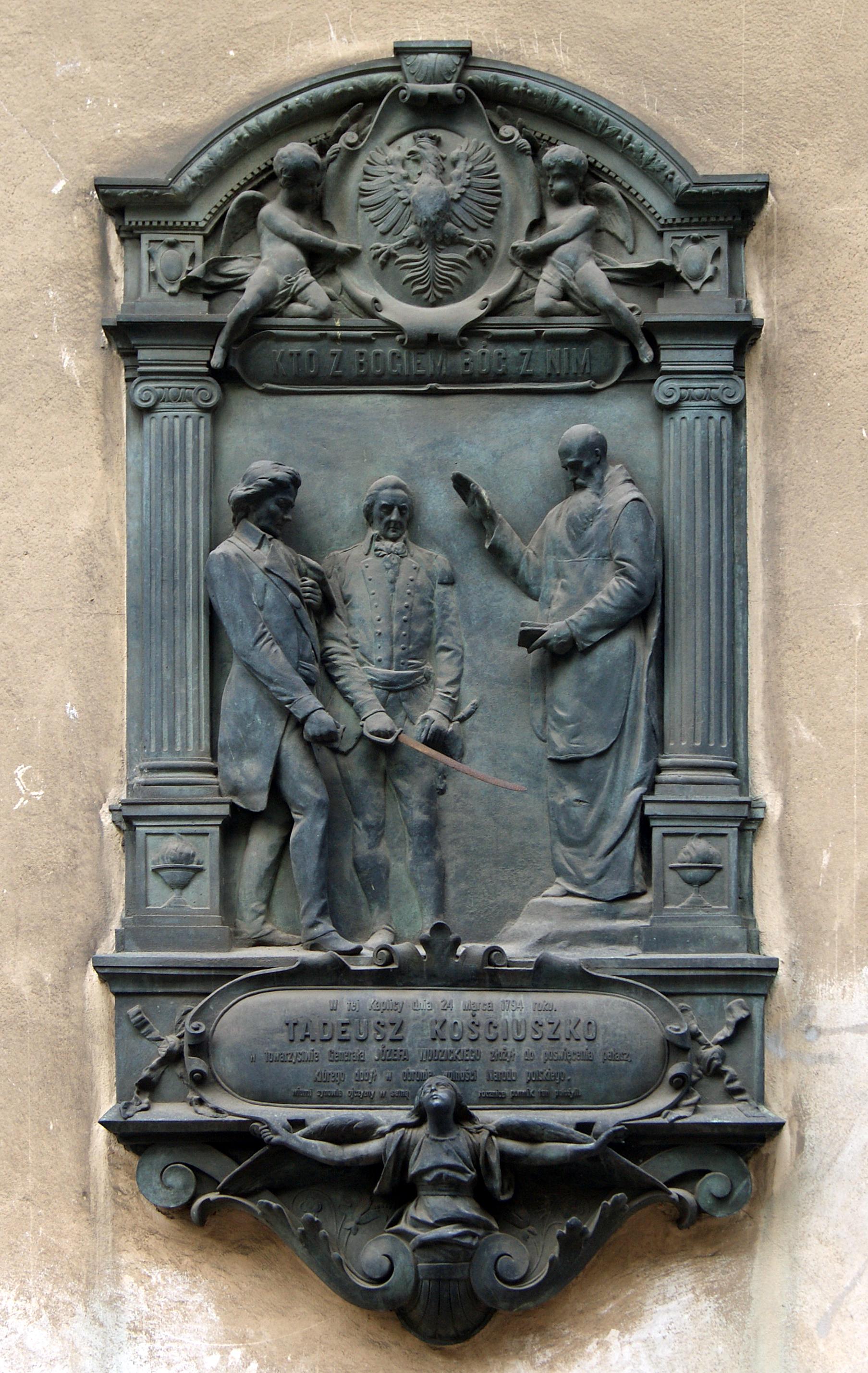 """Tablica pamiątkowa """"Święcenie pałaszy"""", źródło: wikipedia.pl"""
