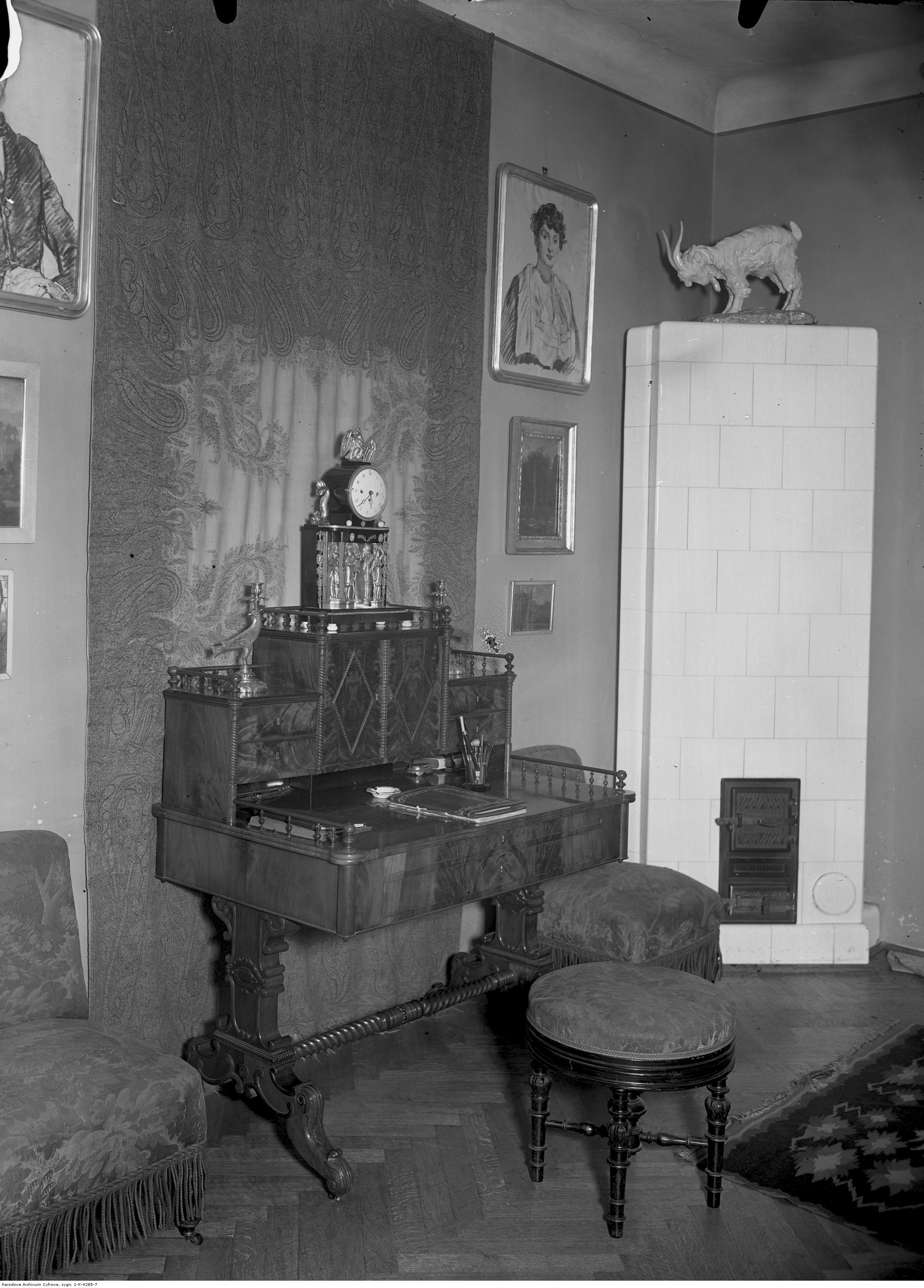"""Wnętrze mieszkania Józefa Mehoffera, na piecu widoczna rzeźba Konstantego Laszczki """"Capek"""", źródło: Narodowe Archiwum Cyfrowe"""